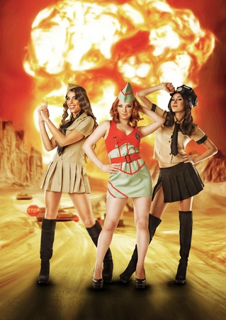 Three military females standing near nuke explosion photo