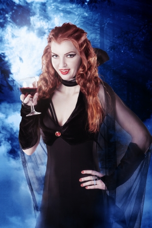 Sexy vampire girl with glass of blood in the woods at night