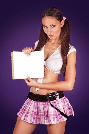 erotic dress: Sexy schoolgirl holding an open book showing a blank paper copyspace