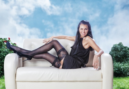 sexy brunette laying on a couch wink in black dress on a garden Stock Photo