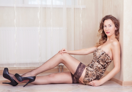 Cute woman lying on the floor stockings and leopard dress photo