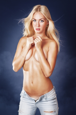 topless jeans: Cute blond woman standing topless covering breast over blue background Stock Photo