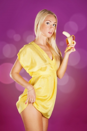 Cute blond woman holding a banana ready to eat over pink background  photo