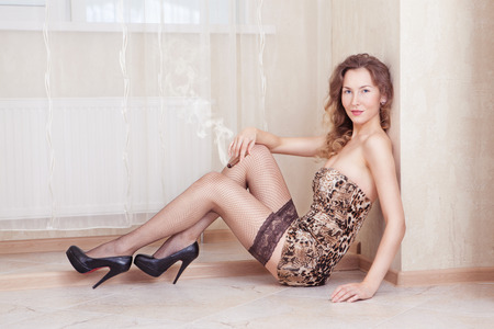 Cute woman lying on the floor smoking a cigar stockings and leopard dress photo