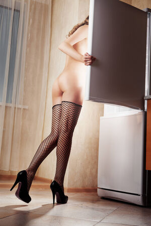 Sexy nude woman looking for food in the fridge at night photo