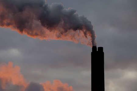 billow: Smoke billowing from a power station chimney, illuminated at sunrise