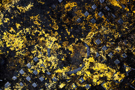 daubed: A cast iron manhole cover daubed with tarmac and yellow paint