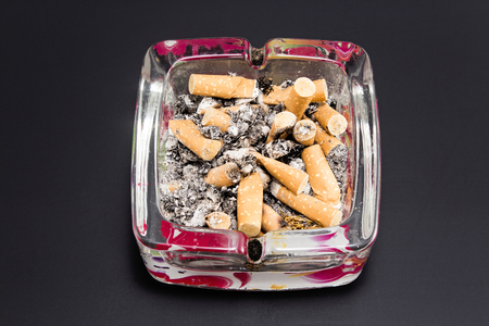anti smoking: An ashtray with cigarette butts on a black background. Stock Photo