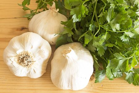 garlics: Garlics and parsley on the plank table