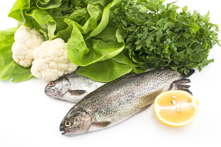 rainbow trout: Two rainbow trout with vegetables and lemon.