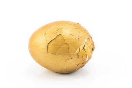 financial burden: Broken gold egg on a white background.