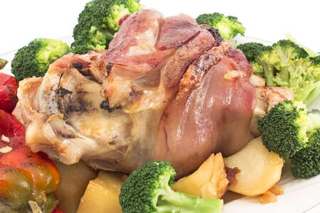 Baked pork knuckle with vegetables. Stock Photo