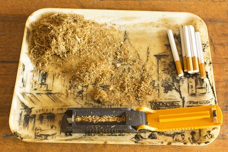 manually: Manually making cigarettes with the tobacco machine. Stock Photo