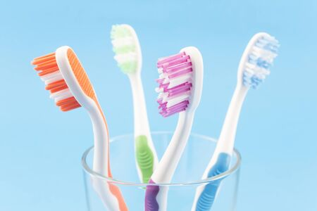 Colourful toothbrushes isolated on blue.
