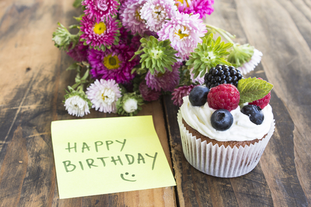 Delicious Cupcake with Happy Birthday Notepaper and Flowers. Stock Photo