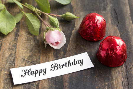 short phrase: Happy Birthday Card with Two Pralines and Rose. Stock Photo