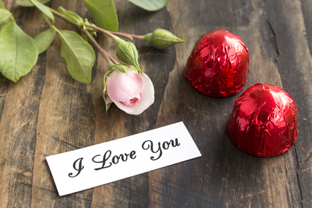 short phrase: I Love You Card with Two Pralines and Rose. Stock Photo