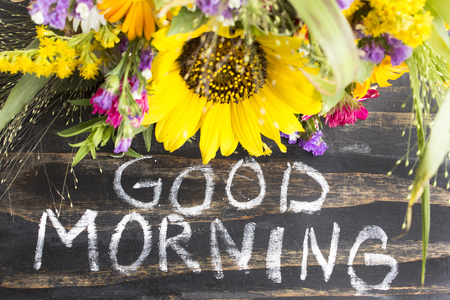 short phrase: Words Good Morning with Summer Flowers on a Rustic Wooden Background.