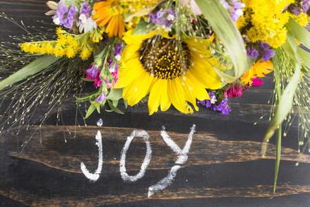 gleeful: Word Joy with Summer Flowers on a Rustic Wooden Background.