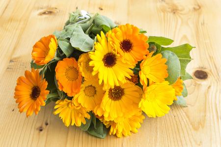 longevity drugs: Marigold, Calendula Officinalis on a Wooden Table.