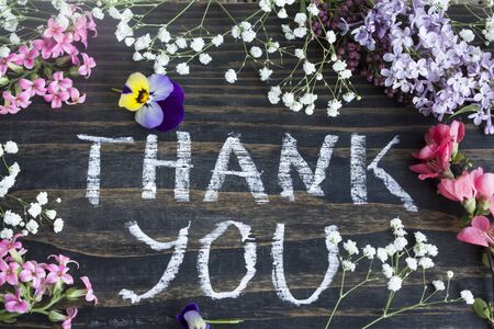 short phrase: Words Thank You with Spring Flowers on a Rustic Wooden Background. Stock Photo