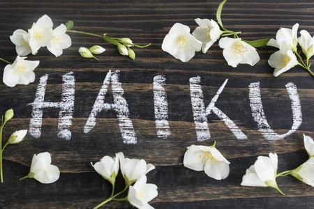 haiku: Word Haiku, Japanese Poetry, with Jasmine Flowers on a Rustic Wooden Background.