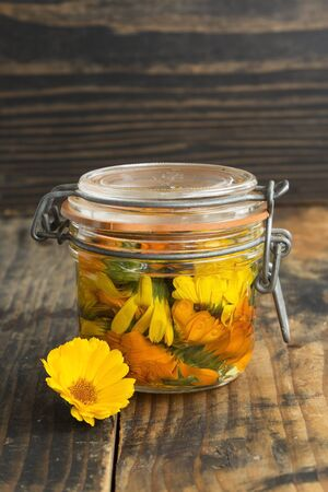 longevity drugs: Calendula Oil in a Jar on a Rustic Wooden Background.