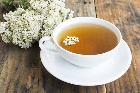 Schafgarbe-Tee, Achillea Millefolium, auf einem rustikalen hölzernen Hintergrund. Standard-Bild - 79085075
