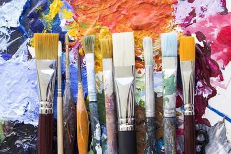 specificity: Concept of Individuality, Various Paintbrushes on a Multicolored Palette Stock Photo