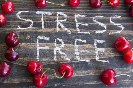 Words Stress Free with Fresh Cherries on a wooden background. Standard-Bild - 102685970
