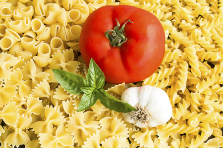 Italian cuisine, Pasta, Tomato, Garlic and Basil as a background. Standard-Bild - 102685983