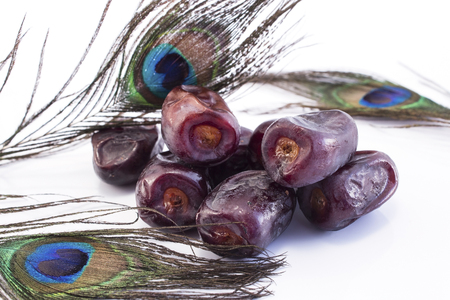 Ripe Dates Fruit with Peacock Feathers on White Background. Standard-Bild - 106147770