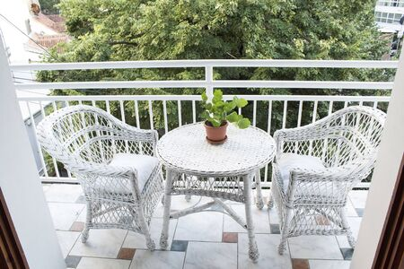 Terrace with Wicker Furniture and a View of the Treetop. Standard-Bild