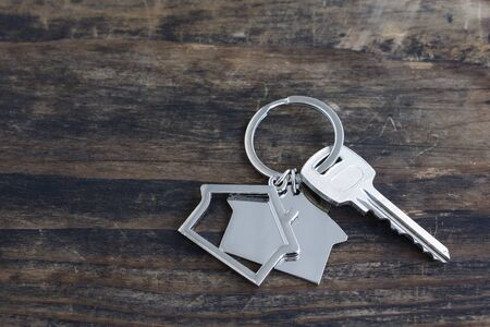 Key and House Pendant on a Rustic Wooden Background. 版權商用圖片