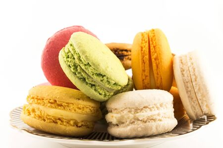 A Pile of Colorful Macaroons on a Plate Isolated on White Background.