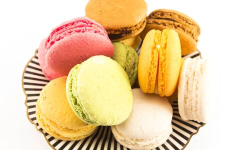 A Pile of Colorful Macaroons on a Plate on White Background.