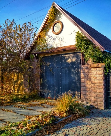 damaged roof: Old house with large entrance doors in autumn. In the courtyard of the old house fallen yellow leaves.
