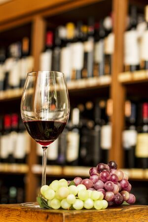 Wine glass, grape and bottles on the background  photo