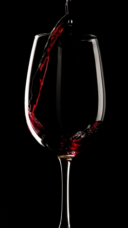 Glass of red wine on black background  photo