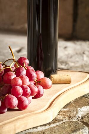 Wine cups, cork, bottle of wine, wood, grapes and fire on the background  photo