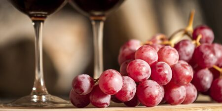 Wine cups, cork, bottle of wine, wood, grapes and fire on the background Stock Photo - 19410095