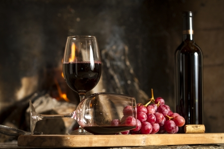 Drinking red wine, grapes, bottle and cork on wooden board background with fire photo