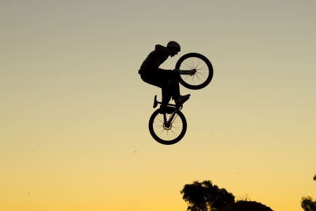 Silhouette of a young man performing a radical mountain bike jump photo