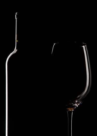 Elegant wine bottle and wine glass, cup, in a black background photo