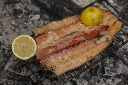 fish husbandry: Trout with lemon on the fire on a camping Stock Photo