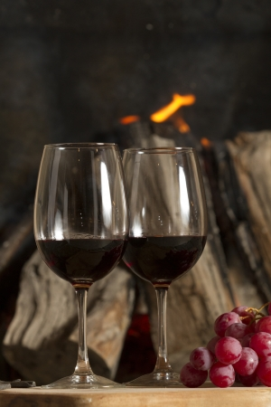 Wine glasses, Grapes, cork and a bottle of wine over a wooden table with fire on the background  Stock Photo