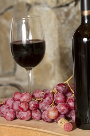 Wine glasses, Grapes, cork and a bottle of wine over a wooden table with fire on the background Stock Photo - 20127900