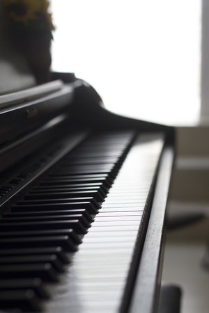 Piano side view with keys lost in the light  Stock Photo