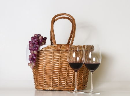 Glasses of wine, basket and grape over white  photo