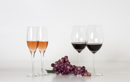 Glasses of wine and grape over white